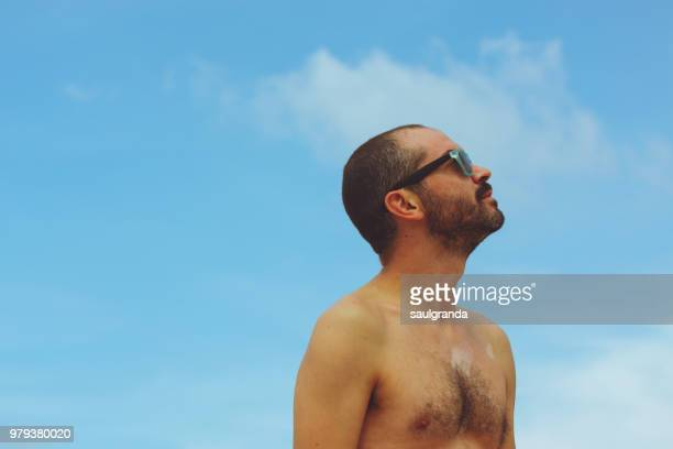 mid adult man with mycosis in his chest looking up against the sky - schimmelinfectie stockfoto's en -beelden