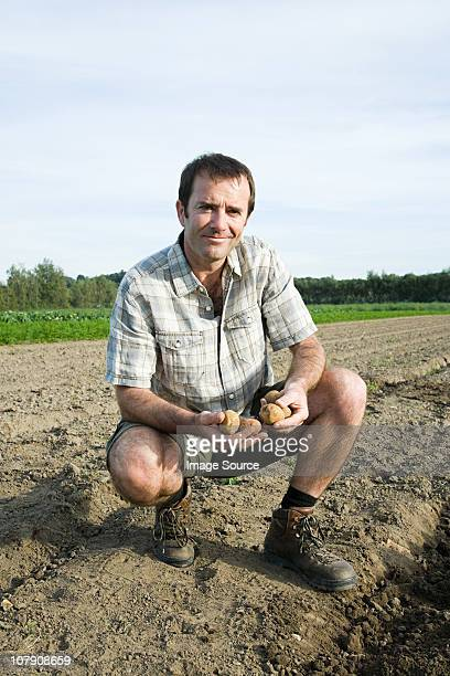 Mid adult man with potatoes in field