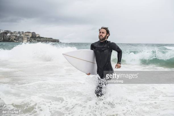 Mid adult man with surfboard running through waves in sea