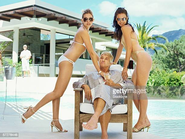 mid adult man with two women in bikinis - sugar daddy stock photos and pictures