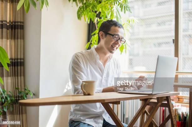 休日に自宅で働く 30 代の男性 - パソコン ストックフォトと画像