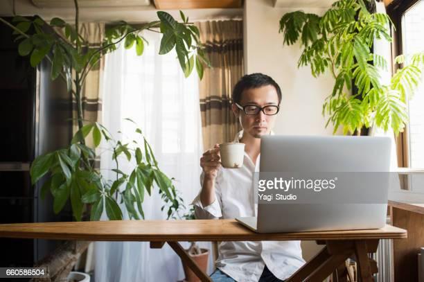 休日に自宅で働く 30 代の男性