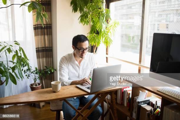 休日に自宅で働く 30 代の男性 - テレワーク ストックフォトと画像