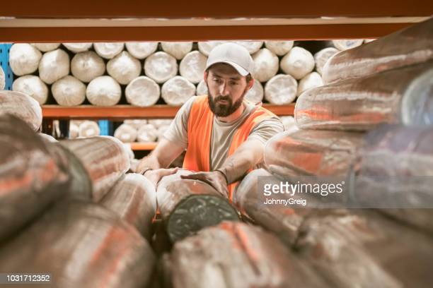 mid adult man working in carpet factory inspecting products - man wrapped in plastic stock pictures, royalty-free photos & images