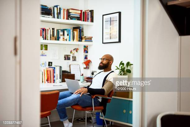 mid adult man working in home office with laptop - strategy stock pictures, royalty-free photos & images