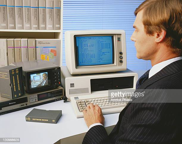Mid adult man working on old computer and watching video