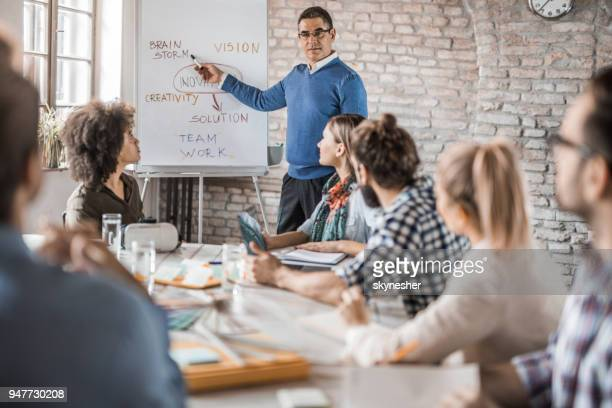 Mid adult manager giving a presentation to his colleagues in the office.