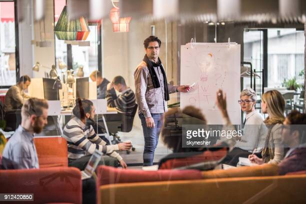 mid adult manager giving presentation to his coworkers in the office. - staff meeting stock pictures, royalty-free photos & images