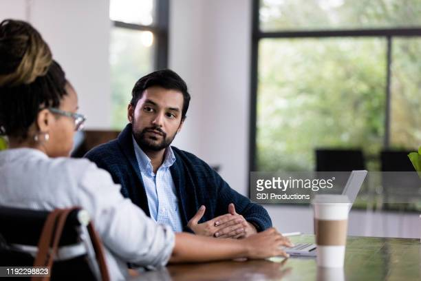 mid adult manager meets with male employee for progress report - serious stock pictures, royalty-free photos & images