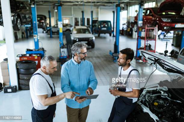 mid adult manager using touchpad and talking to car mechanics in a workshop. - auto repair shop stock pictures, royalty-free photos & images