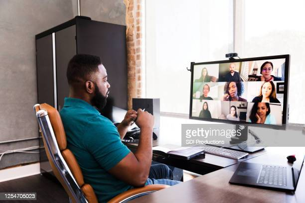 mid adult manager video conferences with his team - black ethnicity stock pictures, royalty-free photos & images