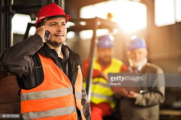 Mid adult manual worker communicating over cell phone in factory.