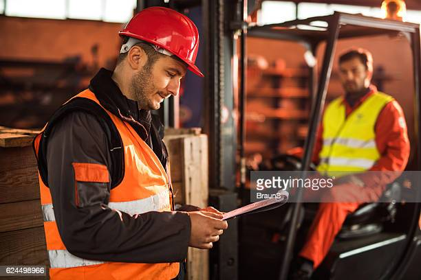 Mid adult manual worker reading reports in a factory.