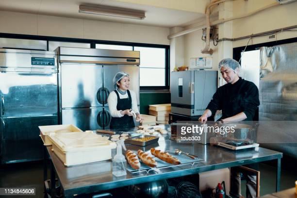 中小企業のベーカリーのための工業用キッチンで一緒にベーキング半ば大人の結婚カップル - パン屋 ストックフォトと画像