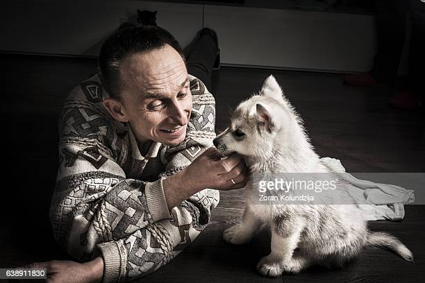 mid adult men playing with husky puppy - homme soumis photos et images de collection