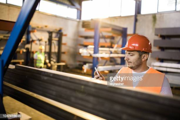 mid adult metal worker using cell phone in a factory. - candid forum stock pictures, royalty-free photos & images