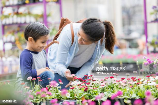 Mid adult mom shops for flowers with son