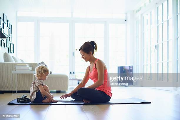 Mid adult mother and toddler daughter practicing yoga in living room