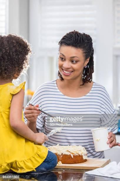 meados adulta mãe goza de um bolo de confeiteiro com filha - fazer um bolo - fotografias e filmes do acervo