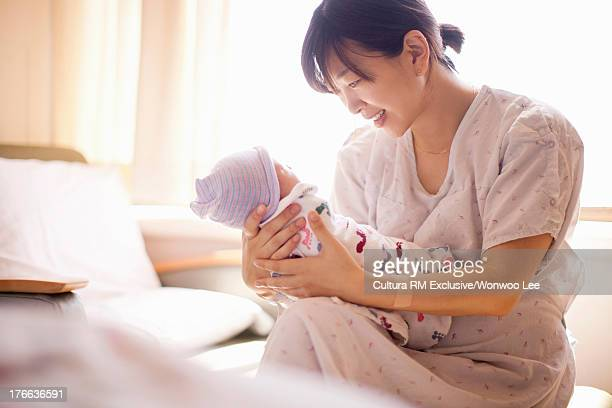 Mid adult mother holding newborn baby girl, smiling