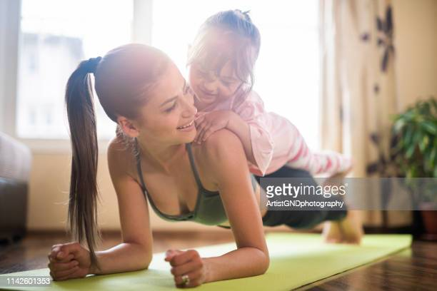 mid adult mother practicing yoga with toddler daughter on top of her, beautiful mother and daughter training home workout - exercising stock pictures, royalty-free photos & images