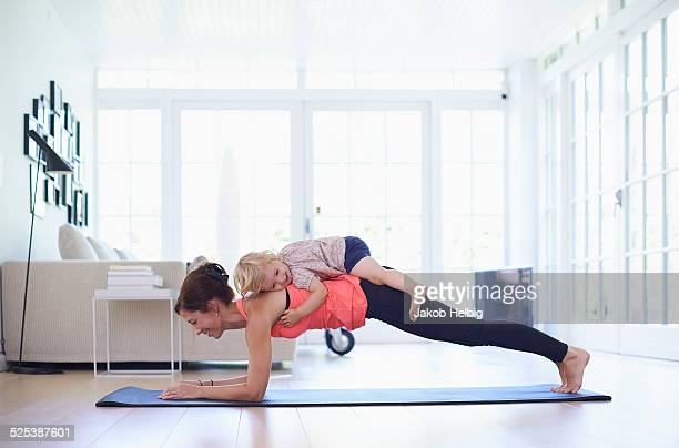mid adult mother practicing yoga with toddler daughter on top of her - routine stock-fotos und bilder
