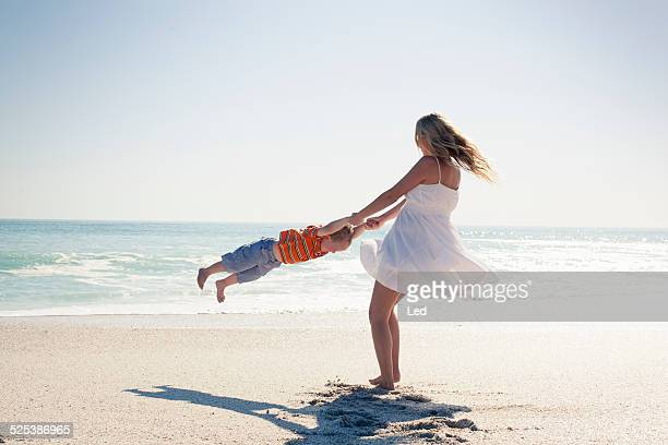 mid adult mother swinging young son by hands on beach, cape town, western cape, south africa - blue shorts stock pictures, royalty-free photos & images