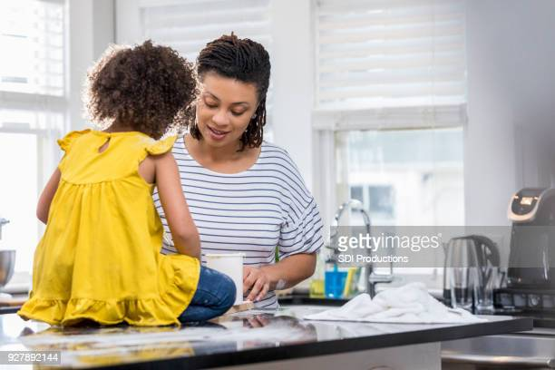 Mid adult mother teaches young daughter how to bake
