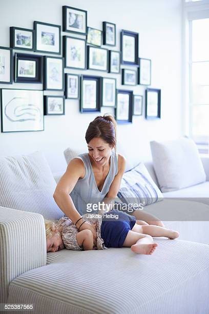 Mid adult mother tickling toddler daughter on sofa