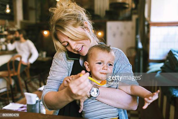 mid adult mother trying to feed baby boy in restaurant - multi tasking stock pictures, royalty-free photos & images