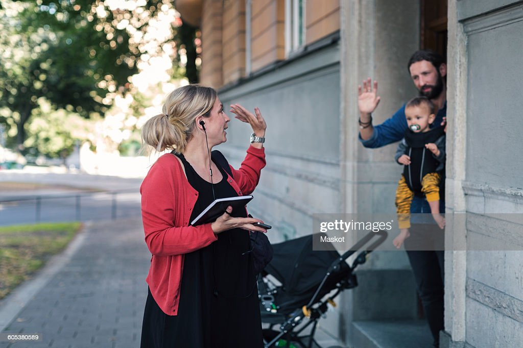 Mid adult mother waving family while leaving for work : Stock Photo