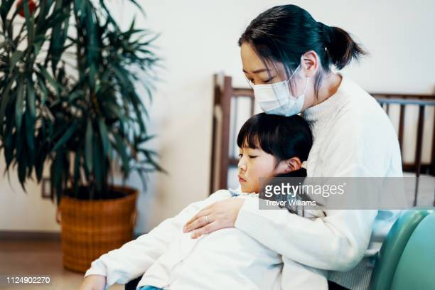 mid adult mother with young daughter in a hospital waiting room - 身体症状 ストックフォトと画像