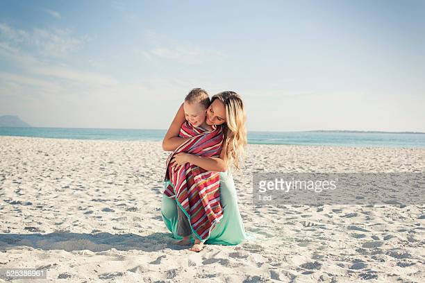mid adult mother wrapping son in a towel at beach, cape town, western cape, south africa - wrapped in a towel stock pictures, royalty-free photos & images