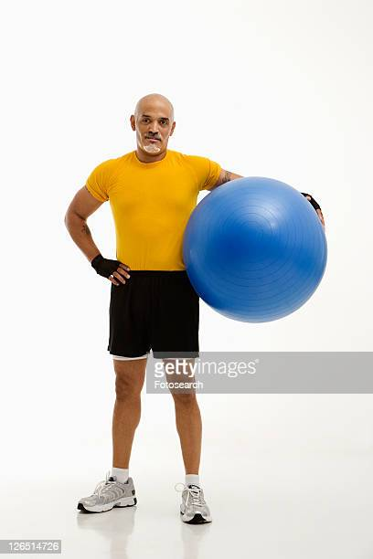 mid adult multiethnic man standing and holding blue exercise ball looking at viewer. - blue balls pics stock pictures, royalty-free photos & images