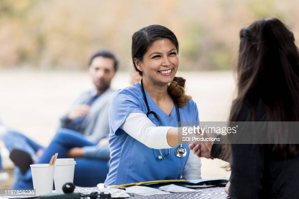 mid adult nurse shakes hands with patient at free clinic - selfless stock pictures, royalty-free photos & images