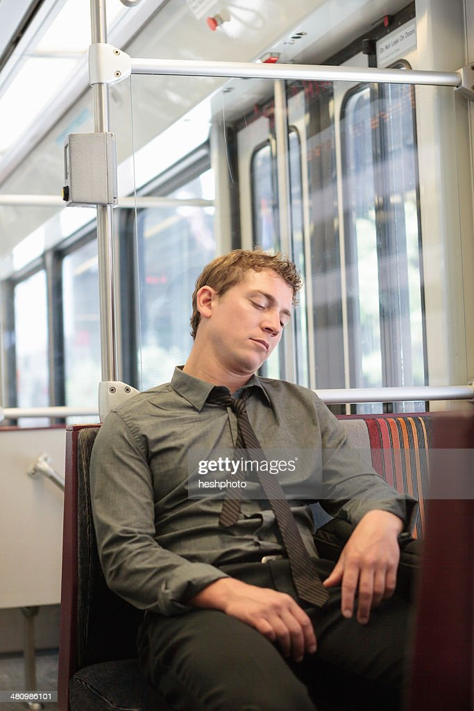Mid adult office worker snoozing on train journey : Stock Photo