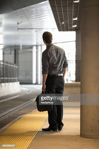 mid adult office worker watching for train at station - heshphoto photos et images de collection
