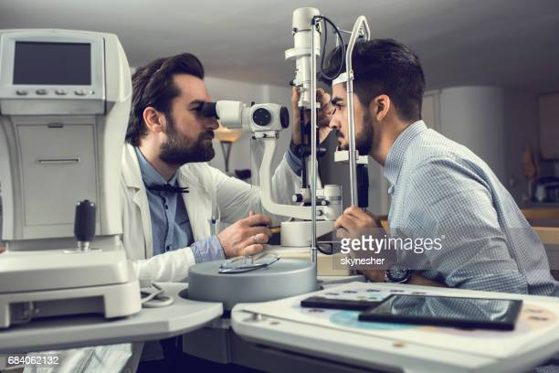Mid adult ophthalmologist measuring an eyesight of a young man with diagnostic medical tool.