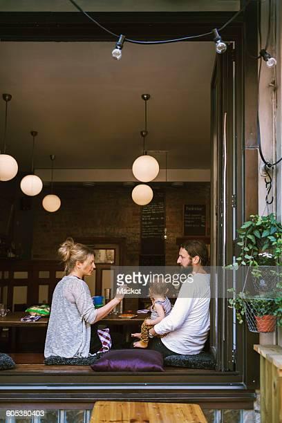 Mid adult parents feeding son in restaurant seen through window