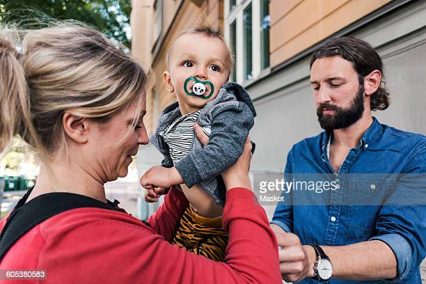 Mid adult parents with baby boy outside house