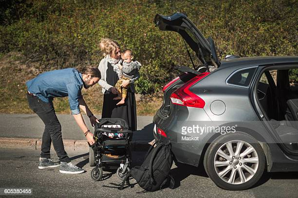 Mid adult parents with son and baby carriage near car on street