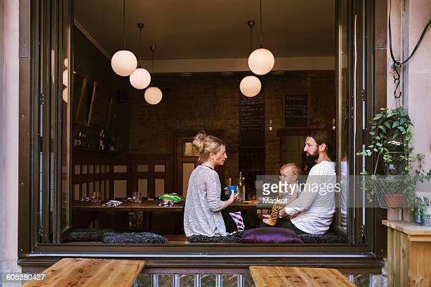 Mid adult parents with son in restaurant seen through window