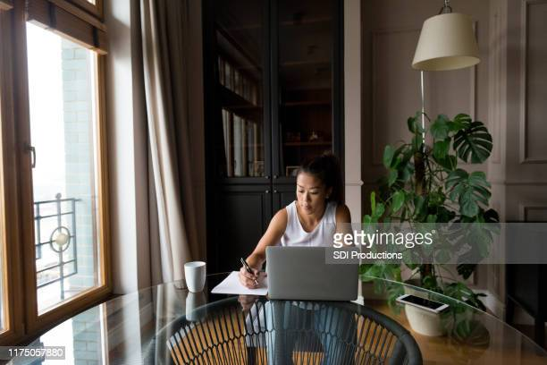 mid adult pregnant woman does freelance work from apartment - pregnant coffee stock pictures, royalty-free photos & images