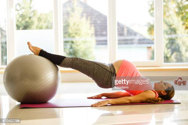 Mid adult pregnant woman is exercising