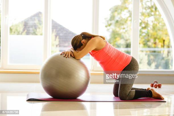 mid adult pregnant woman is exercising with a ball - labor childbirth stock photos and pictures
