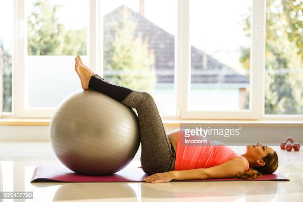 Mid adult pregnant woman is exercising with a fitness ball