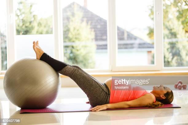 mitte adult schwangere frau übt mit einem fitnessball - frau gespreizte beine stock-fotos und bilder