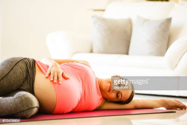 Mid adult pregnant woman is lying on an exercise mat