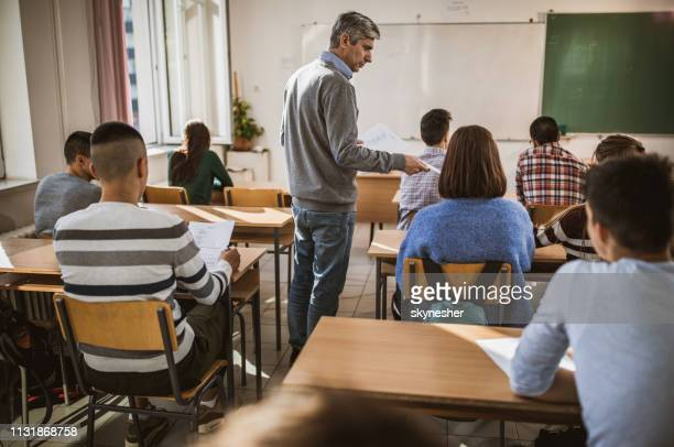 mid adult professor giving exam papers to his students in the classroom. - high school building stock pictures, royalty-free photos & images