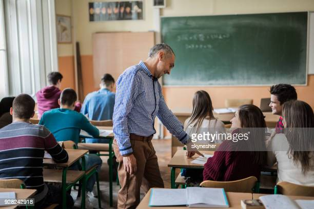 mid adult professor helping his students during a class at high school. - insegnante foto e immagini stock
